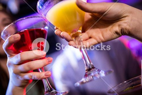 Friends toasting cocktail at bar counter