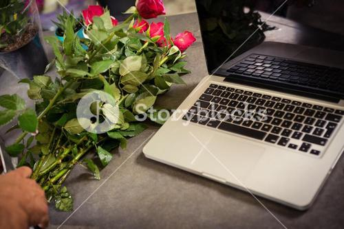 Worktop with laptop and bunch of roses at flower shop
