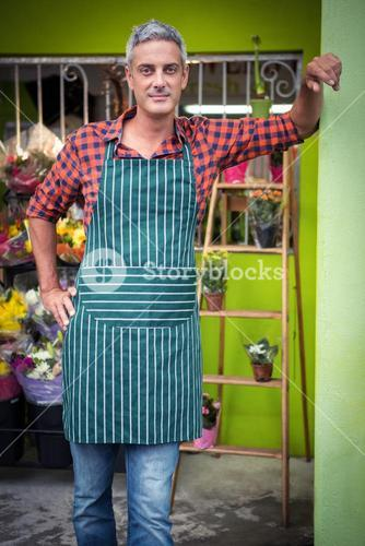 Male florist with hands on hip at flower shop