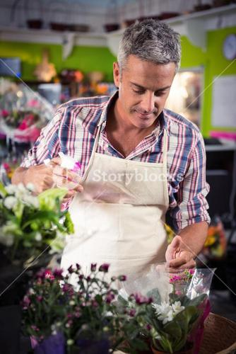 Male florist spraying water on flowers