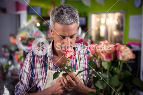 Male florist smelling flower