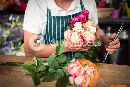 Male florist holding bunch of roses and shears