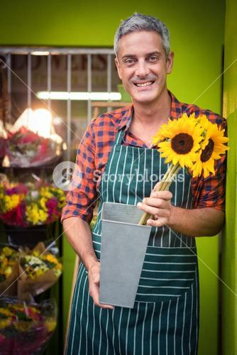 Male florist holding flower vase at flower shop
