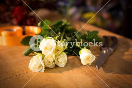 Bunch of roses with shears and poly ribbon on the wooden table