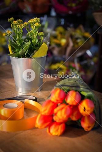 Bouquet of flower with scissor and poly ribbon on the wooden table