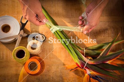 Male florist tying poly ribbon on bunch of flowers