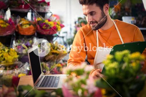 Male florist checking order in laptop
