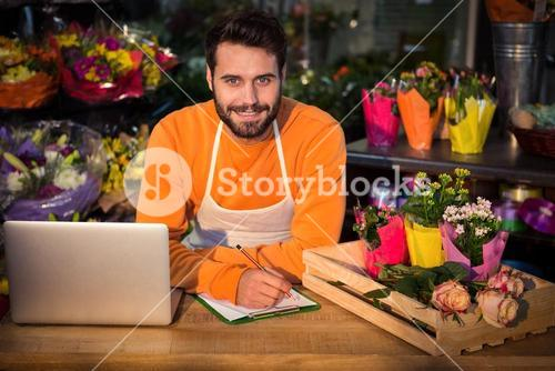 Male florist noting order in notepad
