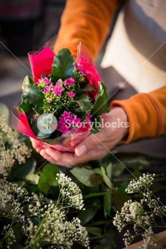 Male florist holding flower bouquet at flower shop