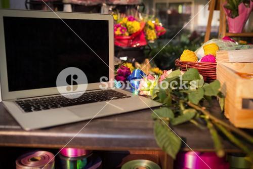 Laptop and florist supplies on the table