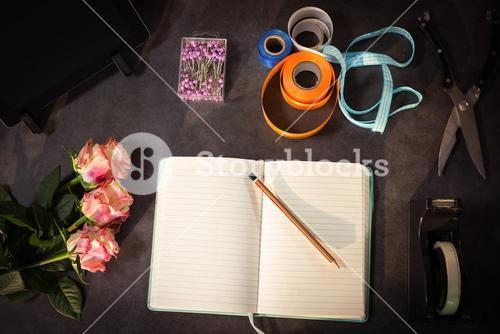 Open diary and florist accessories on the table