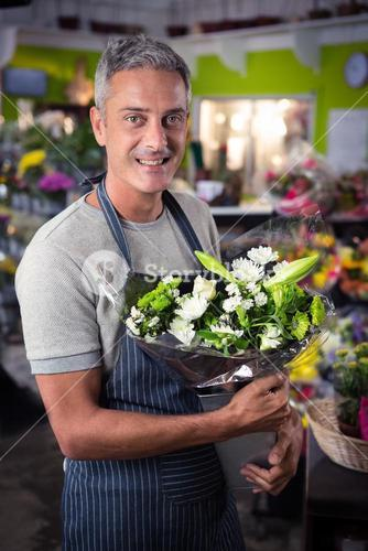 Male florist holding bunch of white flower in vase
