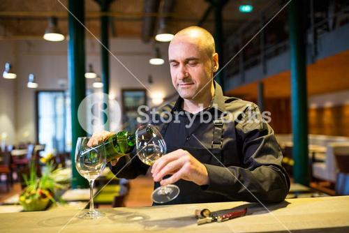 Waiter pouring white wine into glass