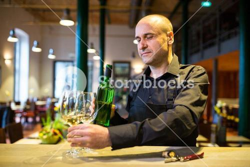 Waiter holding glasses and a bottle of white wine