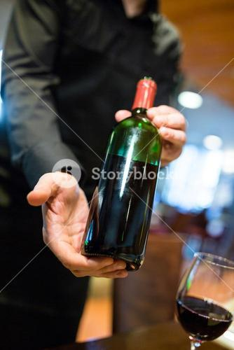 Waiter holding a bottle of red wine