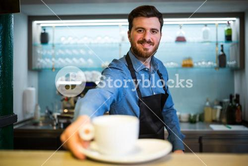 Waiter offering cup of coffee