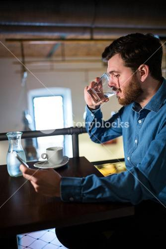 Man having water while text messaging on mobile phone