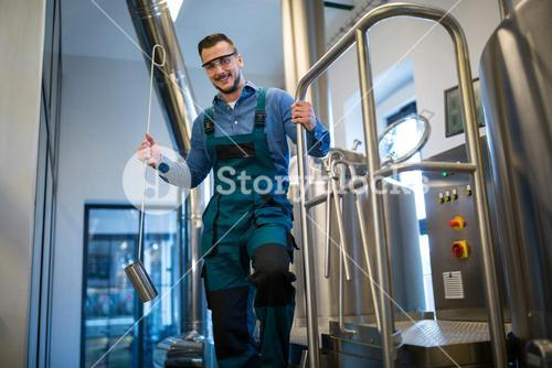 Brewer holding working equipment at brewery