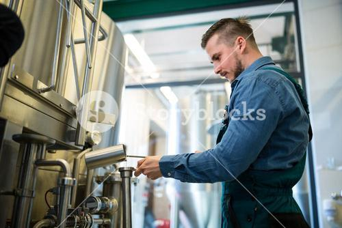 Brewer checking beer at brewery
