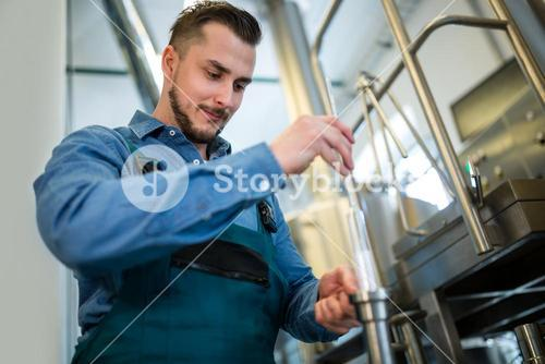Brewer checking beer with hydrometer