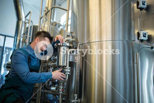 Brewer checking pressure at brewery