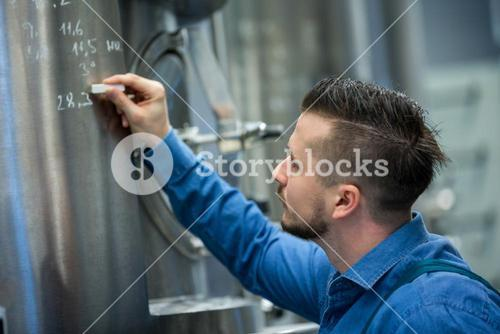 Maintained worker writing on tank