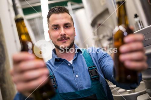 Brewer holding two beer bottle