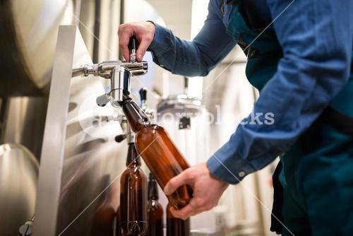 Brewer filling beer in bottle