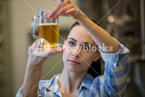 Close-up of female brewer testing beer