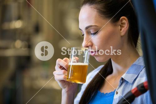 Female brewer testing beer