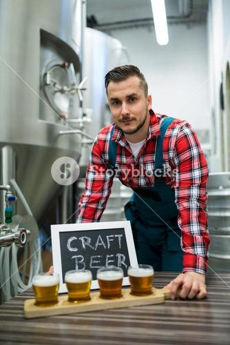 Portrait of brewer with four glasses of craft beer on table