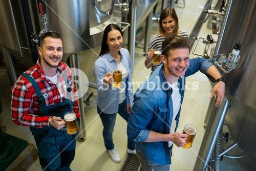 Brewers holding glass of beer standing at brewery