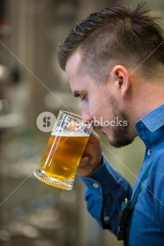 Close-up of brewer testing beer