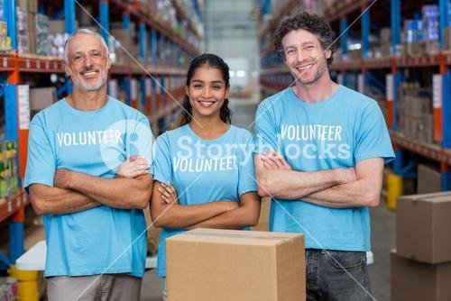 Happy volunteer are posing with crossed arms