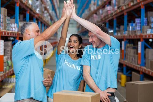 Happy volunteers are clapping hands each other