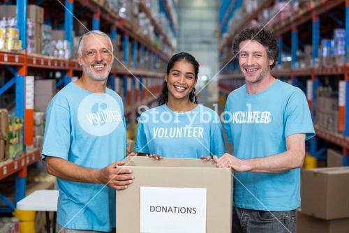 Happy volunteers are smiling and posing with a donations box
