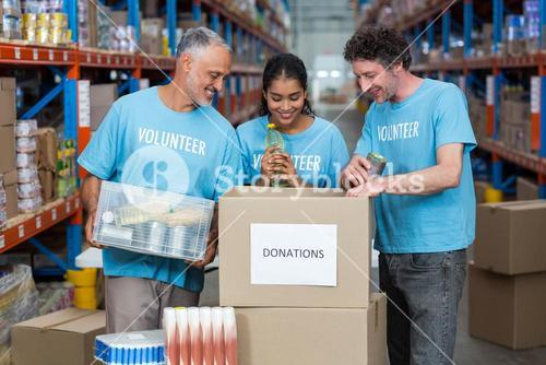 Happy volunteers are looking inside a donations box