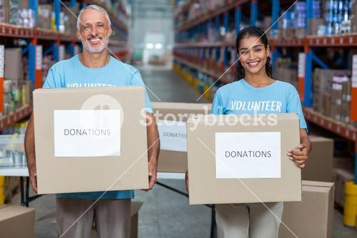 Happy volunteers are smiling and holding donations boxes