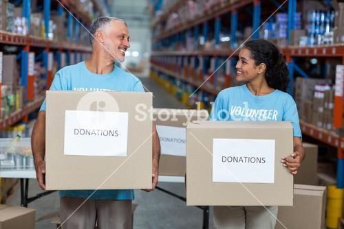 Happy volunteers are holding donations boxes and looking each other