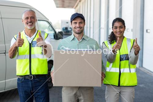 Portrait of workers are posing with thumbs up close to a delivery man