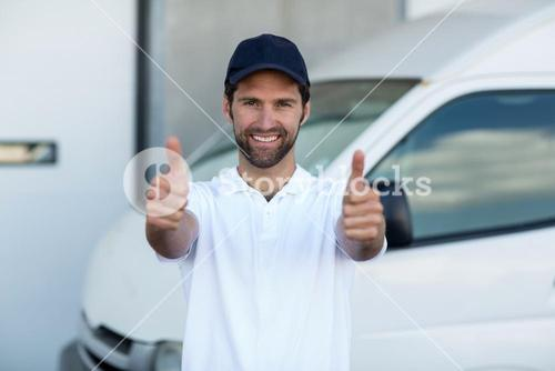 Portrait of delivery man is posing and smiling with thumbs up