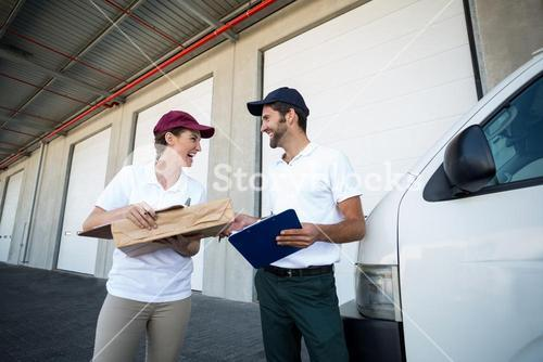 Low angle view of delivery people are looking each other and laughing