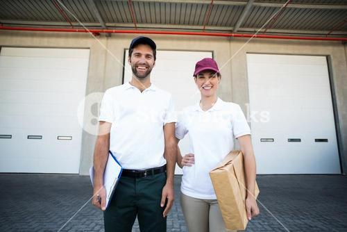Delivery people are posing and smiling