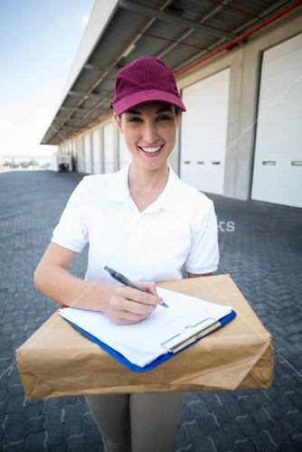 Portrait of delivery woman is holding a cardboard box and smiling to the camera