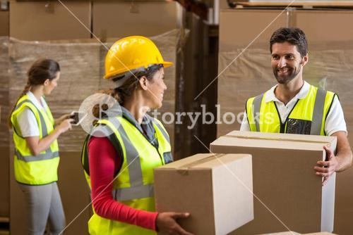 Portrait of workers are holding cardboard boxes and looking each other