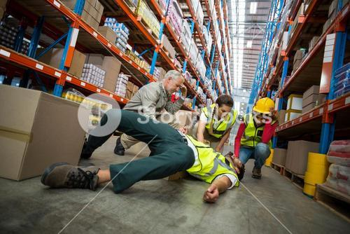 Workers taking care about their colleague lying on the floor