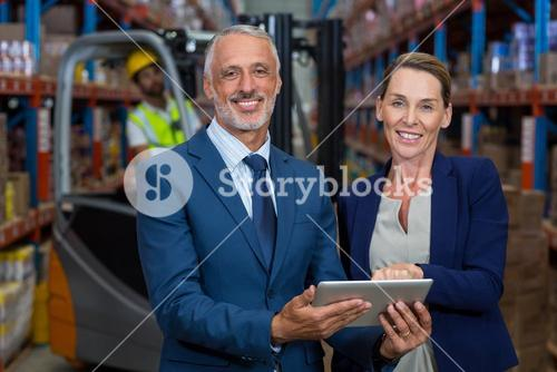 Portrait of happy managers holding a tablet and looking the camera
