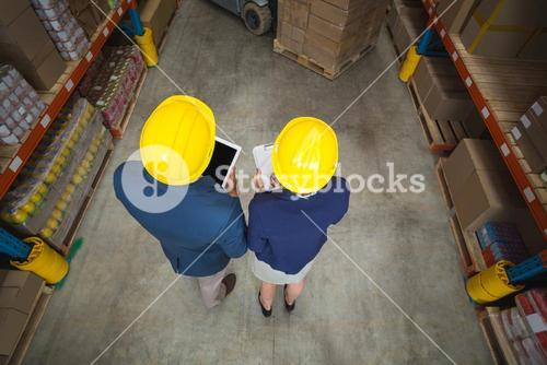 High angle view of managers with hard hat holding tablet and clipboard