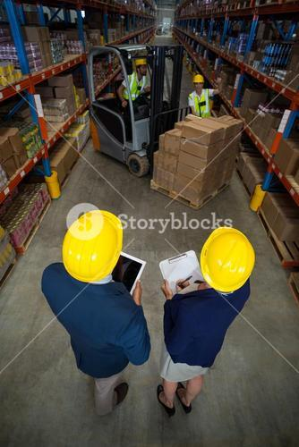 High angle view of manager wearing hard hat and looking workers