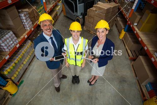 High angle view of managers and worker wearing hard hat and looking the camera
